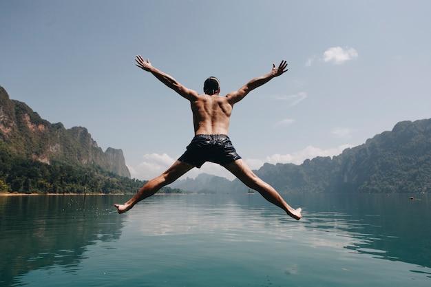 Человек, прыгающий с радостью у озера