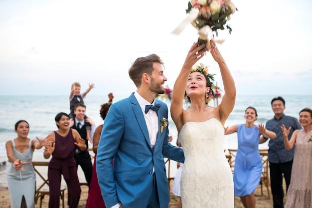 ビーチでの結婚式の若いカップル