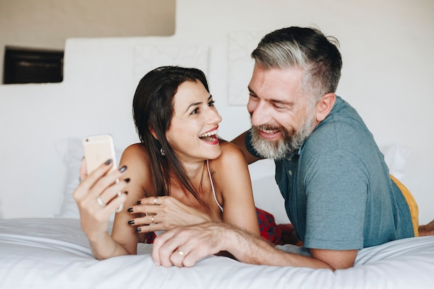 ベッドでスマートフォンを使っているカップル