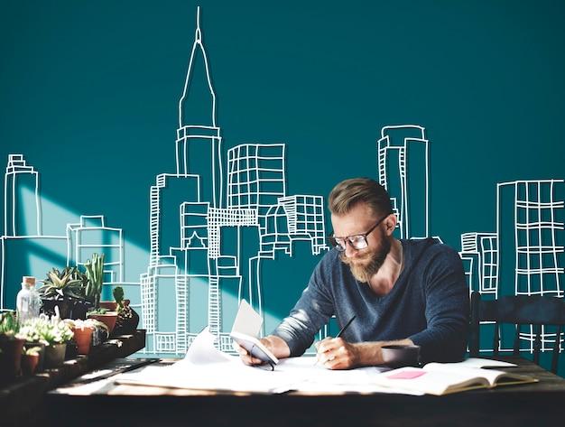 緑の背景にイラストを建てて作業している白人の男
