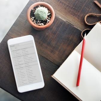 トップビューノートブック携帯電話の電子メールテーブルのコンセプト