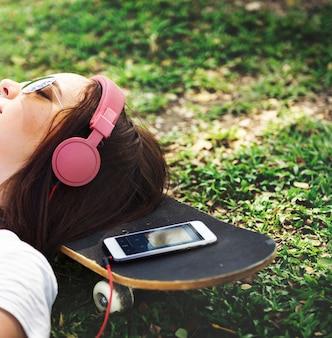 音楽を聴く草の上に横たわっている女性