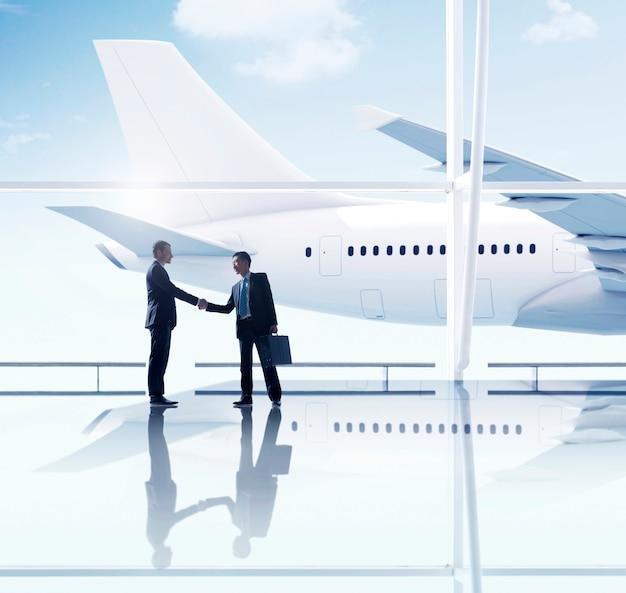 西洋とアジアのビジネスマンハンドシェイク空港ミーティング