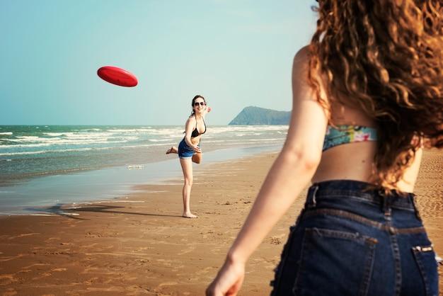 女性はビーチでフリスビーを演奏しています