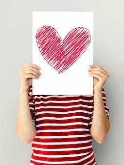 子供が心臓のアイコンを紙につけている