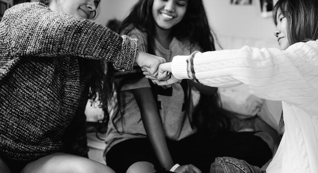 寝室の拳の中の十代の女の子たちが友情コンセプトを打つ
