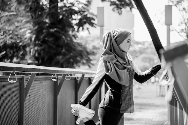 公園での運動の後に伸びるイスラムの女性