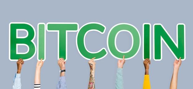 Руки, удерживающие зеленые буквы, образующие слово биткойн