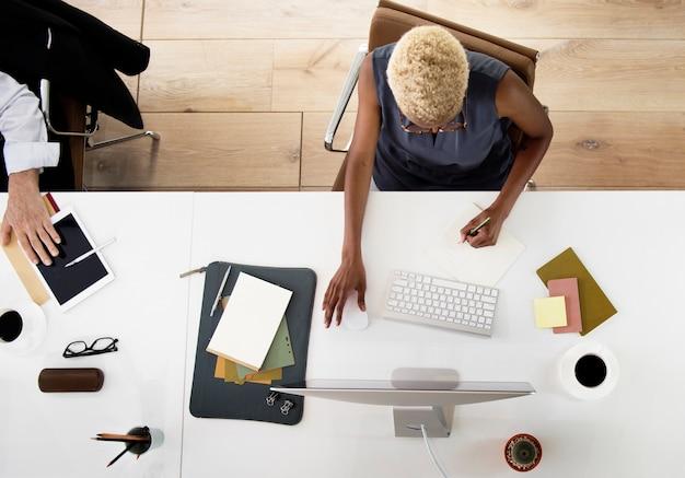 オフィスで白いテーブルでコンピュータ上で働くアフリカ系の降下の女性の航空写真