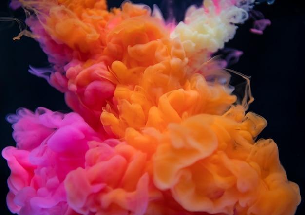 Абстрактный оранжевый и розовый цвет падают в воду