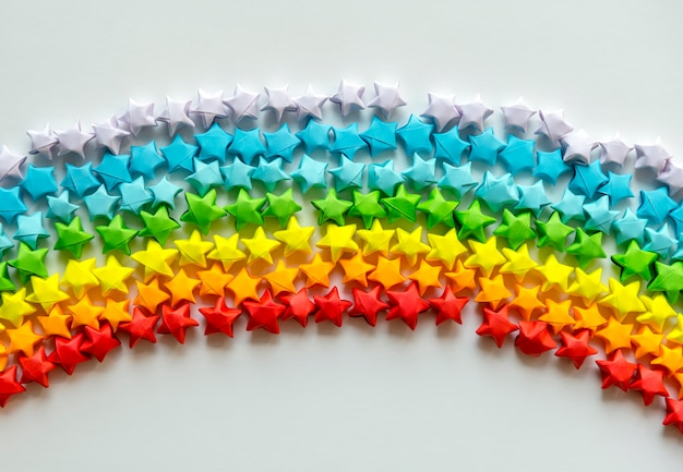 虹の背景を形成するカラフルな折り紙の星