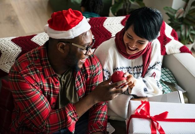 陽気なカップルがクリスマス休暇を楽しんでいます