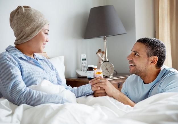 彼女のパートナーとベッドで病気の女性