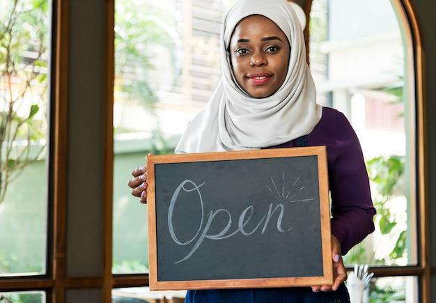 笑顔で黒板を持っているイスラムの女性の中小企業の所有者