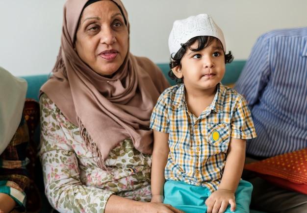 彼の祖母と座っているイスラム教徒の少年