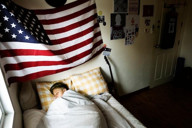 ベッドで寝る若い白人の男の子