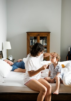 Мальчик сидит на кровати и его мама, проверяя температуру