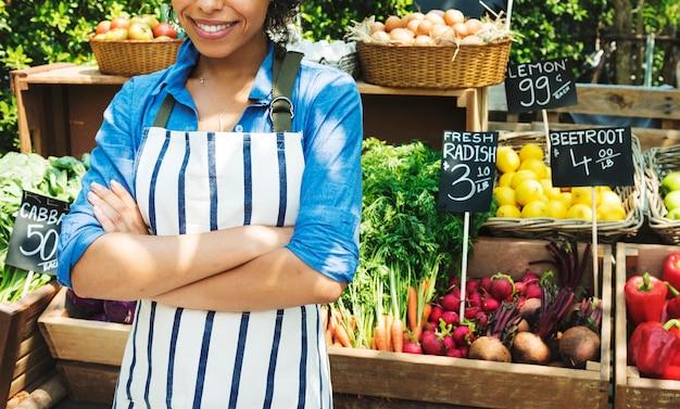 ファーマーズマーケットで新鮮な地元の野菜を売っている女性