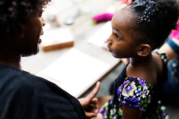 アフリカ系の子孫の少女が先生に聞いている