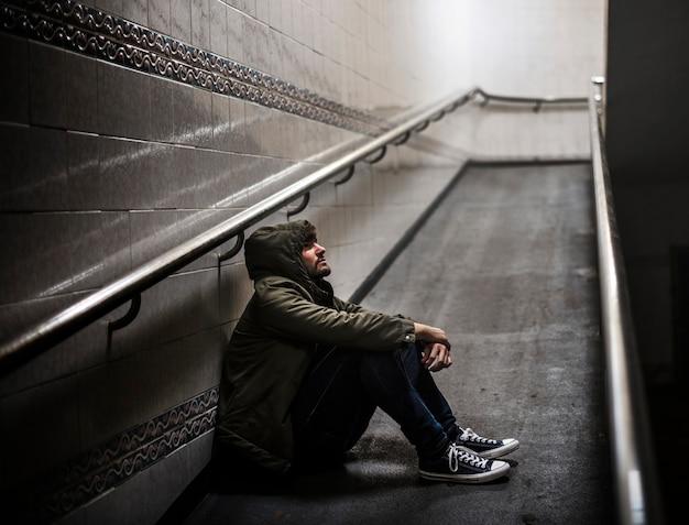 Человек сидит без вести задумчивым на скале