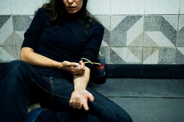 Макрофотография рук с использованием шприца, вводящего наркотические незаконные наркотики