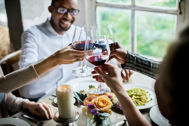 レストランで一緒にワイングラスを抱き締める人々