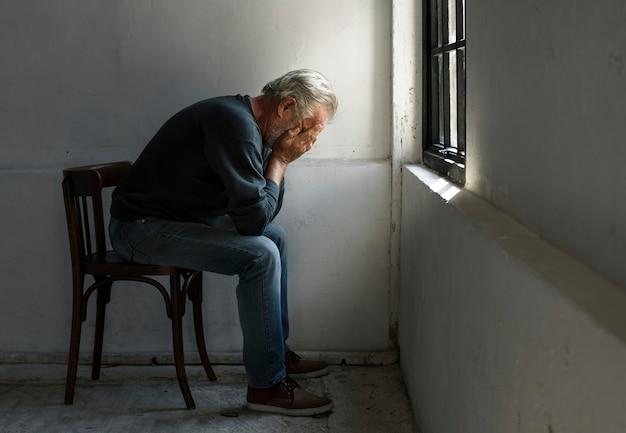 Пожилой кавказский человек с лицом в руках