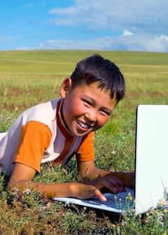 草の上にノートパソコンを持っているモンゴルの少年。
