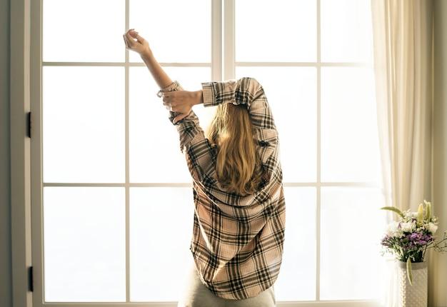 朝の彼女の腕を伸ばしている女性のリアビュー