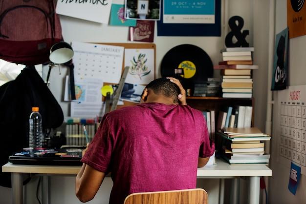 仕事をしているベッドルームの十代の少年は、ストレスとストレス