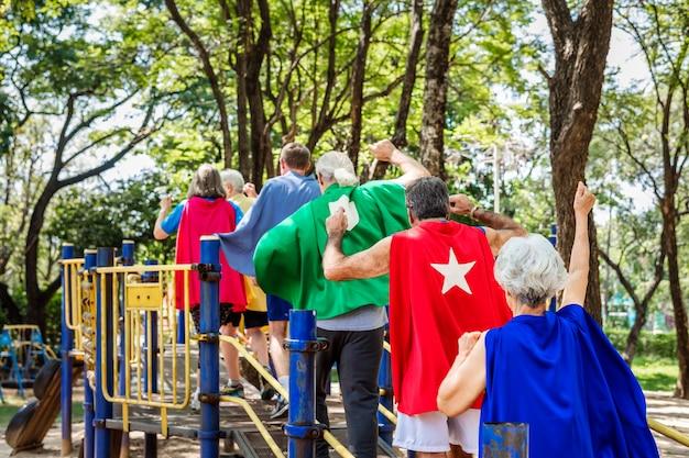 Счастливые пожилые люди в костюмах супергероев на детской площадке