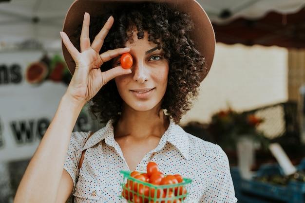 美しい女性が農家市場でトマトを買う