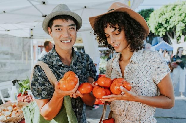 農家市場で新鮮なトマトを買う友人