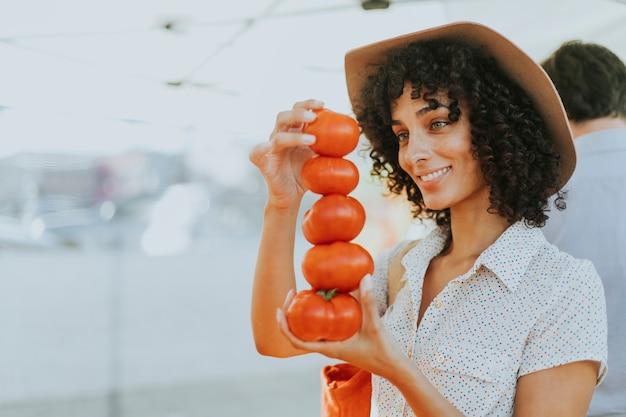 農夫の市場でトマトを買う女性