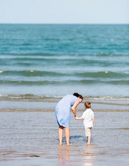母と息子がビーチで寒い