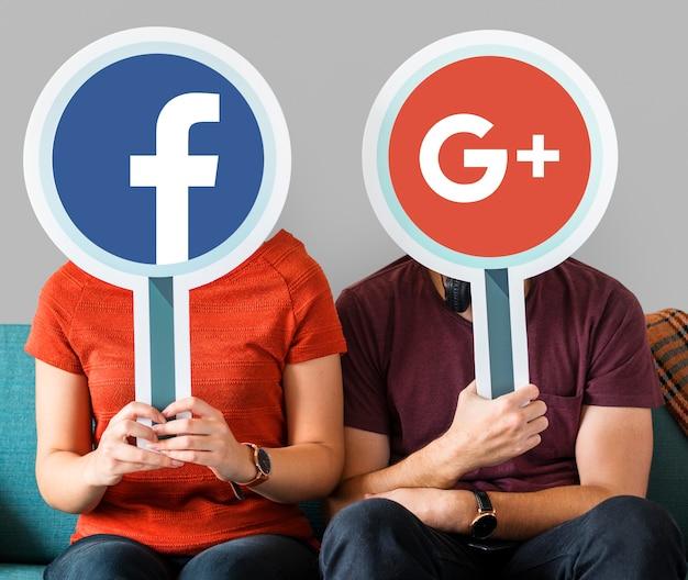 Пара, держащая значки социальных сетей