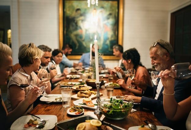 多様な友人のグループが一緒に夕食を食べている