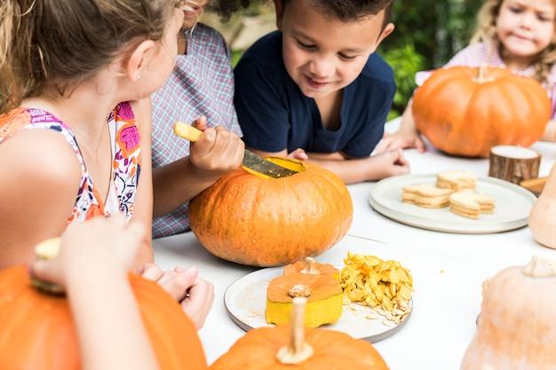 若い子供たちは、ハロウィーンのジャック・オ・ランタンを刻んでいます