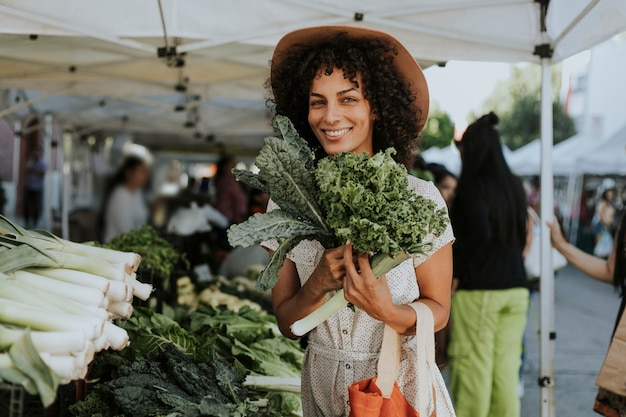 農家市場でケールを買う美しい女性