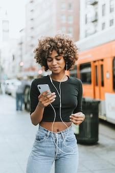 彼女の電話から音楽を聴いている少女