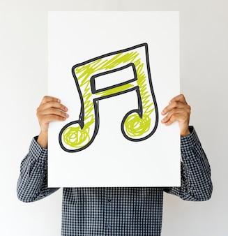 Люди, держащие значок музыки на бумаге