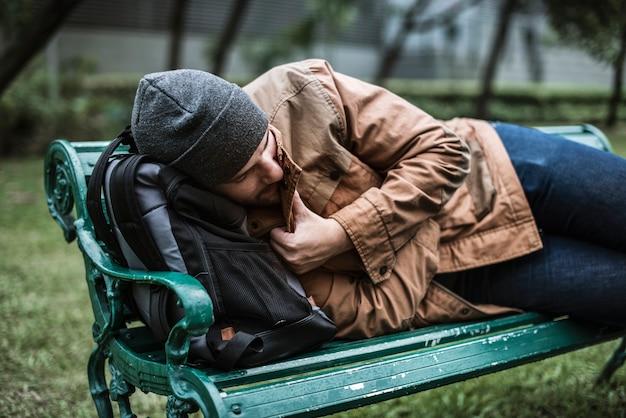 Бездомные спят на скамейке в парке
