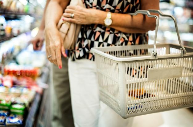 彼女の食料品買い物をしている女性を閉じます