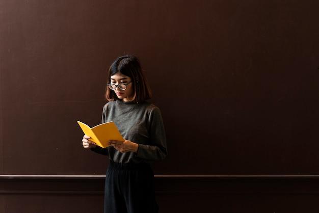 本を読んでいる眼鏡を持った少女