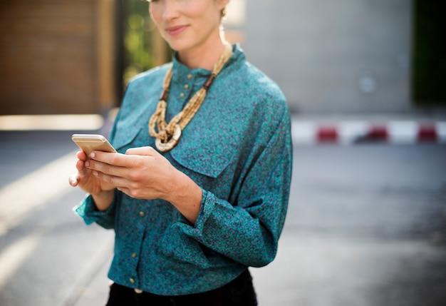 Бизнесмен, стоя и с помощью мобильного телефона