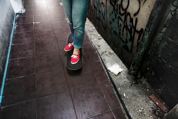 通りの路地のスケートボードに立っている人