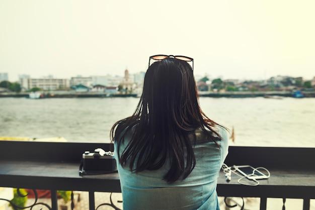 Вид сзади азиатской туристической женщины, сидящей на берегу реки