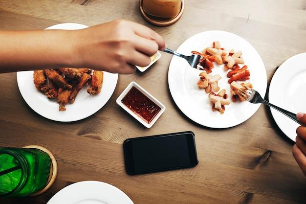 木製のテーブルに食べ物を得る手の航空写真