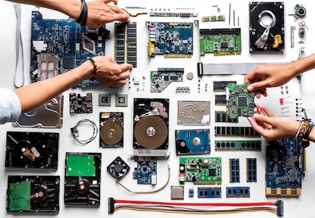 白い背景にコンピュータエレクトロニクス部品で手の航空写真
