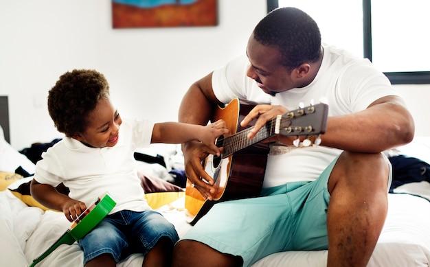 黒人の父は一緒に幸せの彼の子供と一緒にギターを楽しむ